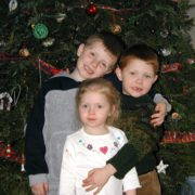 Photo of my 3 kids in front of a Christmas tree when they were little