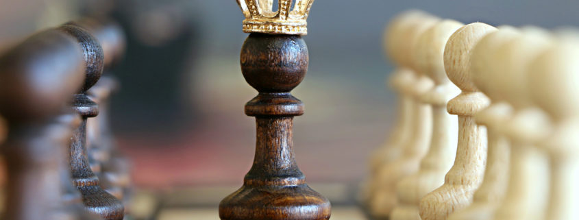 chess board with crowned queen in the middle
