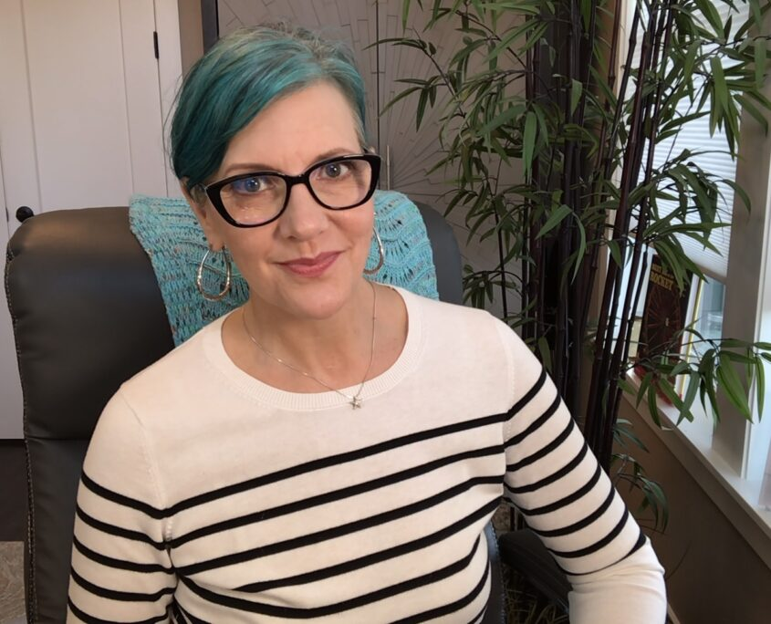 Pretty white woman with teal-colored hair, a striped swearing, large black frame glasses.Sitting in an office chair